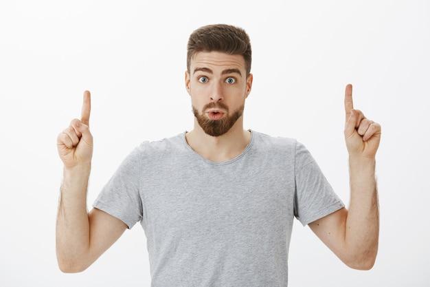 Binnenopname van geïnteresseerde en geïntrigeerde knappe mannelijke man met baard en bruin kapsel die lippen opvouwt van verbazing en nieuwsgierigheid, wijsvingers opheft die omhoog wijst en ondervraagd over grijze muur Gratis Foto