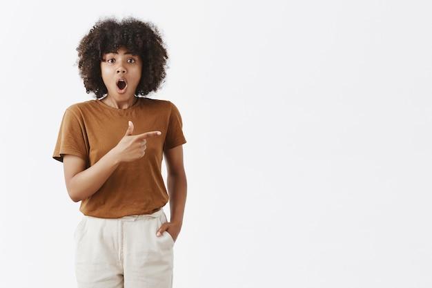 Binnenopname van onder de indruk geëmotioneerd goed uitziend jong afrikaans meisje met zwart krullend haar dat kaak laat vallen van verbazing, naar rechts wijst met een vingerpistool en vraag stelt over wat ze ziet Gratis Foto