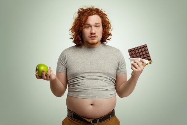Binnenopname van onzekere verwarde mollige jonge man die voor een moeilijke keuze staat, aangezien hij moet kiezen tussen verse biologische appel in de ene hand en heerlijke reep chocola in de andere. dilemma, dieet en voeding Gratis Foto