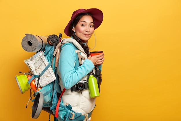 Binnenopname van vrouwelijke reiziger heeft koffiepauze, geniet van reis, draagt rugzak met noodzakelijke dingen en kaart, heeft lange route, draagt hoed en comfortabele kleding Gratis Foto