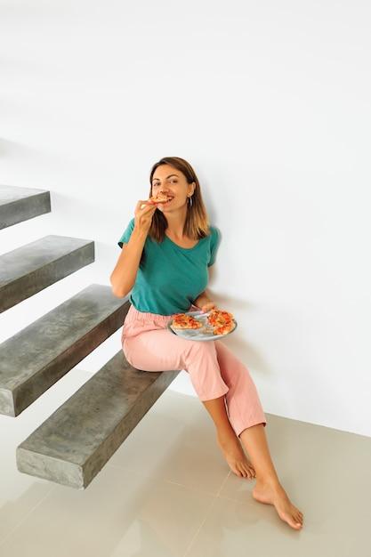Binnenportret die van gelukkige vrouw pizza met kaas eten, die op flor in modern huis zitten Gratis Foto