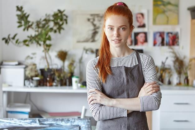 Binnenportret van charmante zelfverzekerde jonge roodharige ambachtenvrouw die een grijze schort draagt die zich in haar atelier bevindt, haar handen gekruist houdt en glimlacht, klaar voor het proces van creatie en hard werken Gratis Foto
