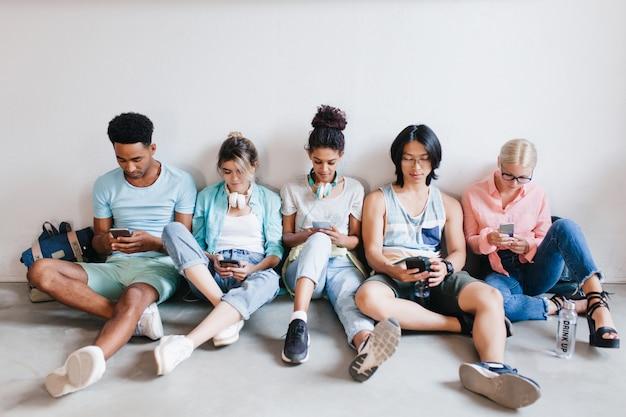 Binnenportret van internationale studenten die wachten op onderzoek en hun telefoon gebruiken. jongens en meisjes die met gekruiste benen op de vloer zitten die apparaten in handen houden. Gratis Foto
