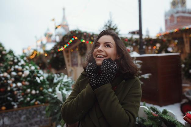 Binnenportret van mooi meisje in rood de winterjasje dat sneeuw op kerstmismarkt blaast Premium Foto