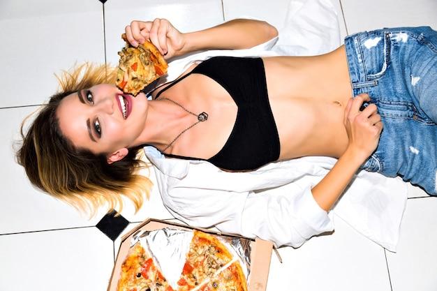 Binnenportret van vrolijke gelukkige jonge vrouw die met stuk van heerlijke hete pizza op vloer leggen. zwart ondergoed, wit overhemd, stijlvolle spijkerbroek. perfect slank lichaam. dieet concept Gratis Foto