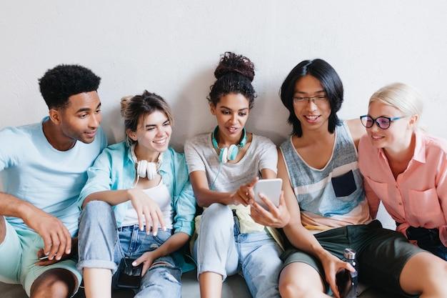Binnenportret van vrolijke studenten die hun telefoons houden en glimlachen. sierlijk afrikaans meisje in oortelefoons en spijkerbroek maken selfie met vrienden op de universiteit. Gratis Foto
