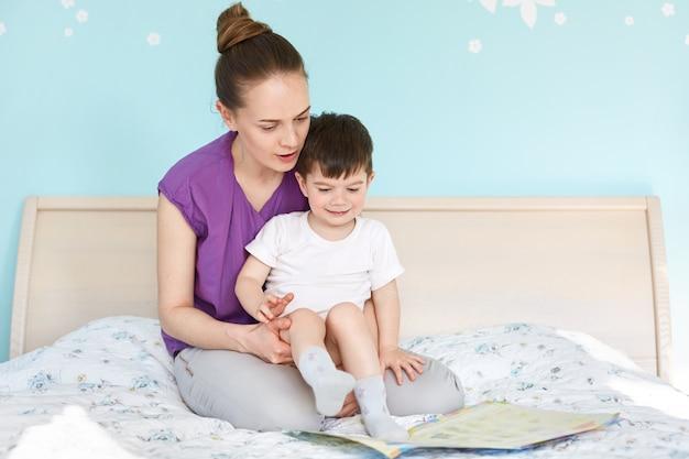 Binnenschot van aanhankelijke jonge moeder houdt en omhelst haar zoontje, bekijk aandachtig het boek met kleurrijke foto's Gratis Foto