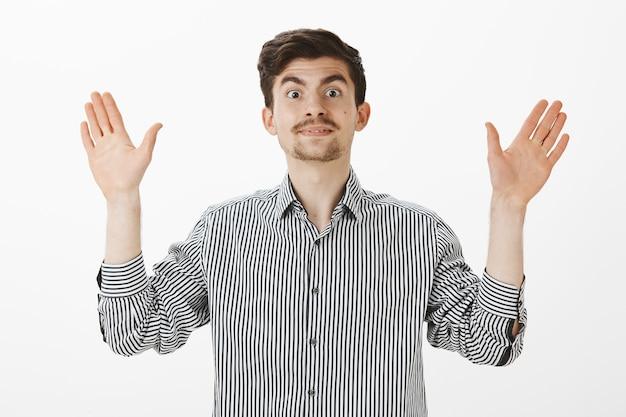 Binnenshuis shot van een emotionele vriendelijke grappige man met baard en snor, die zijn hand opheft in overgave of wil applaudisseren, zich tevreden en gelukkig voelt bij het ontvangen van goede restult, staande over de grijze muur Gratis Foto