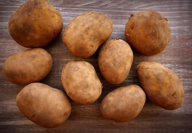 Biologische aardappelen op een houten bord Premium Foto