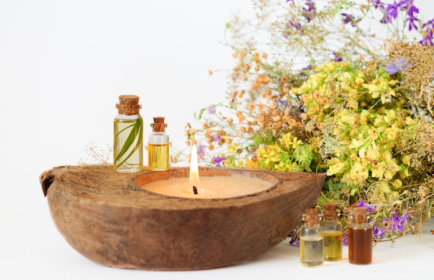 Biologische etherische aroma-oliën in glazen flessen, medicijnkruiden en ecokaars. selectieve aandacht Premium Foto