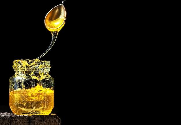 Biologische natuurlijke honing, verlicht door fel zonlicht, in een glazen pot, op een zwarte ondergrond Gratis Foto