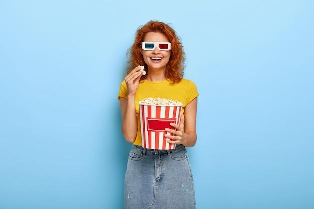 Bioscoopdag en vrije tijdconcept. jonge optimistische roodharige gelukkige vrouw heeft plezier tijdens het kijken naar interessante film Gratis Foto