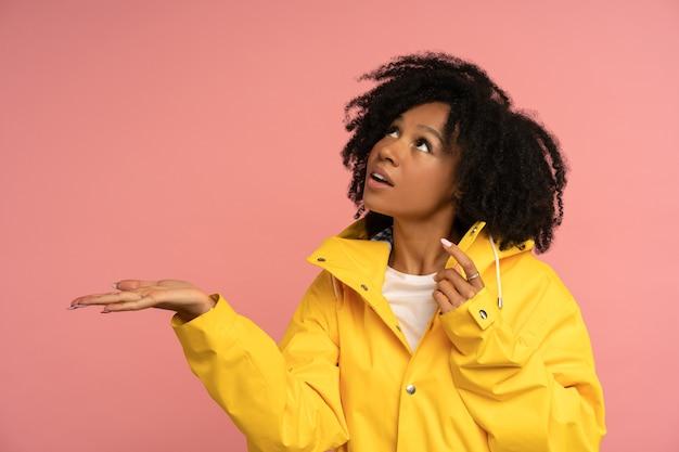 Biracial krullende vrouw in gele regenjas heeft een goed humeur Premium Foto