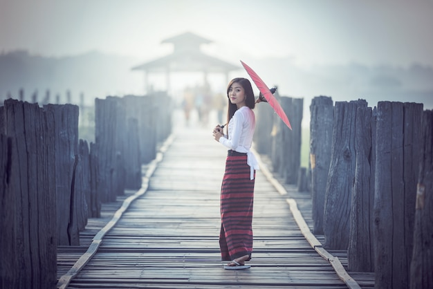 Birmese vrouw die traditionele rode paraplu en lopen op u bein bridge, myanmar Premium Foto