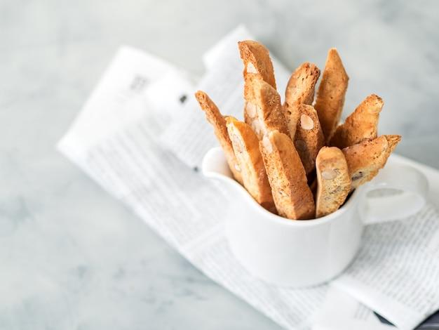 Biscotti (cantuccini) - traditioneel italiaans amandeldessert in witte kopclose-up. Premium Foto