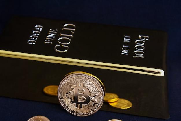 Bitcoin cryptocurrency en goudstaaf op een zwarte achtergrond. Premium Foto