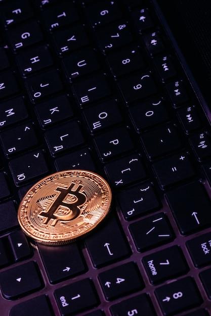 Bitcoin ligt op het toetsenbord van de laptop Premium Foto