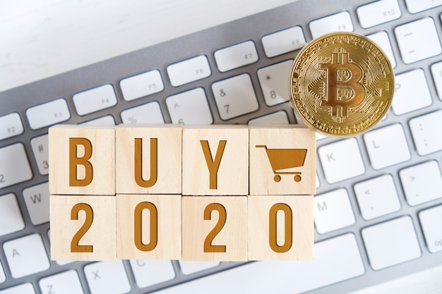 Bitcoin met getallen op houten kubussen op een wit toetsenbord Premium Foto