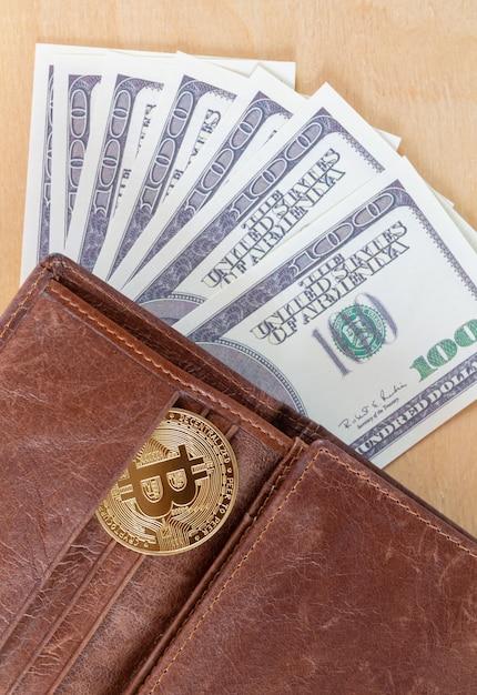 Bitcoin met papieren dollars in portemonnee bovenaanzicht. virtueel cryptocurrency-handels- en investeringsconcept Premium Foto