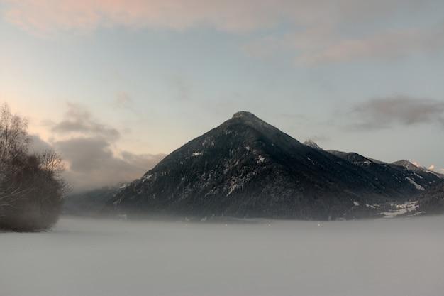 Black mountain onder bewolkte hemel Gratis Foto