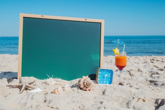 Blackboard en cocktail op het strand Gratis Foto