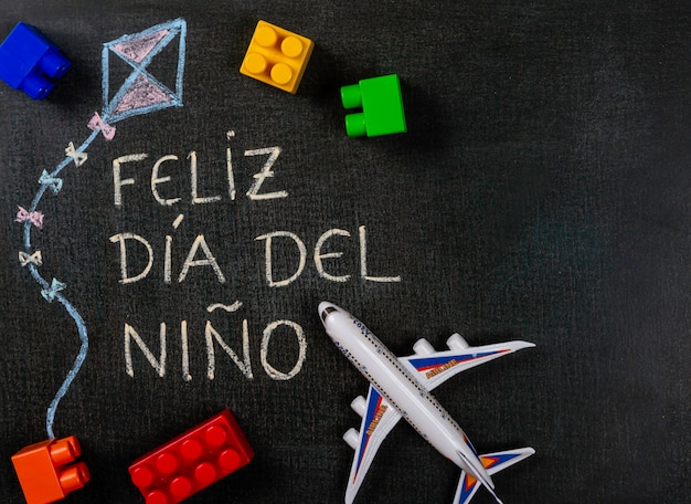 Blackboard geschreven feliz dia del niã ± o (spaans). vliegertekening met speelgoedassemblage en vliegtuigdelen Premium Foto
