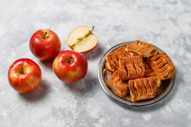 Bladerdeegkoekjes gevuld met appeljam en verse rode appels op licht beton Gratis Foto