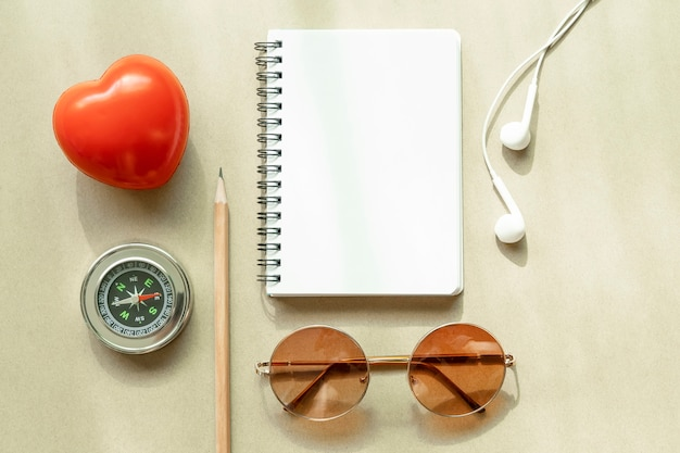 Blanco pagina van geopende witte laptop met kompas, oortelefoon, zonnebril, potlood en rood hart op tafel Premium Foto