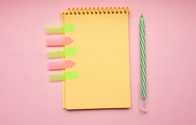 Blanco pagina van verticale spiraal notitieblok met pen op roze Premium Foto