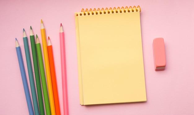 Blanco pagina van verticale spiraal schetsen blok met kleurpotloden op roze Premium Foto