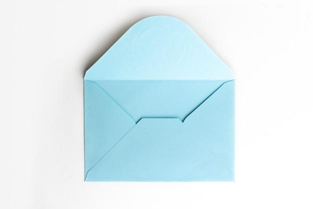 Blanco papier blauwe envelop op wit, plat lag, bovenaanzicht. Premium Foto