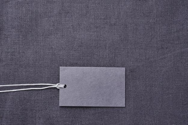 Blanco papier label op grijze linnen kleding Premium Foto