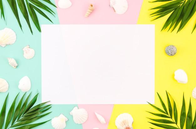 Blanco papier met palmbladeren en schelpen Gratis Foto