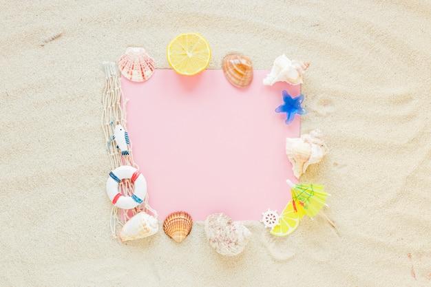 Blanco papier met zeeschelpen op zand Gratis Foto