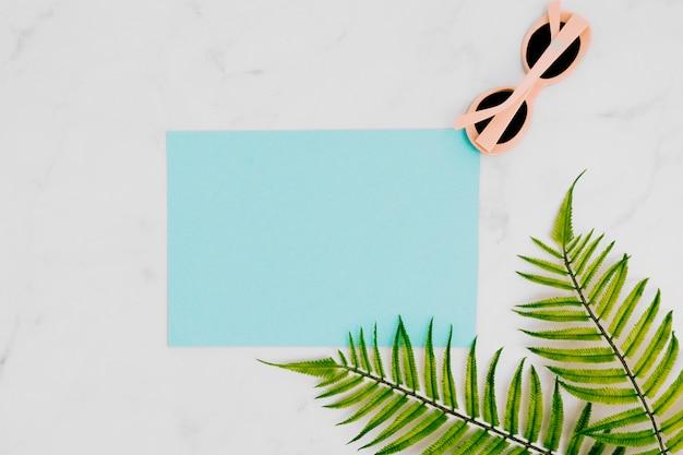 Blanco papier met zonnebril op lichte ondergrond Gratis Foto