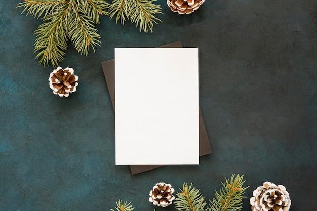 Blanco papier omgeven door dennenbladeren en kegels Gratis Foto
