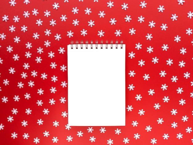 Blanco vel notebook met verspreide witte sneeuwvlokken op rode achtergrond. educatief concept. eenvoudig plat leggen met kopie ruimte. Premium Foto