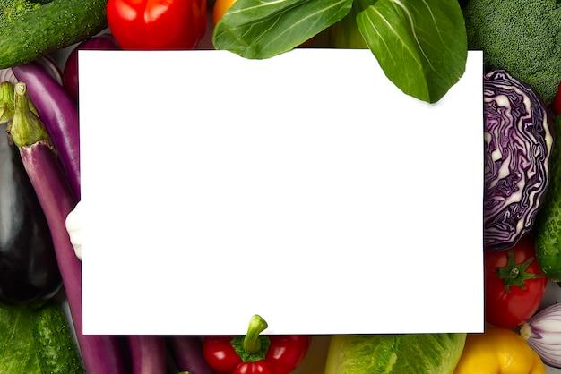 Blanco vel papier ligt op een groenten-indeling met verschillende soorten groenten. Premium Foto