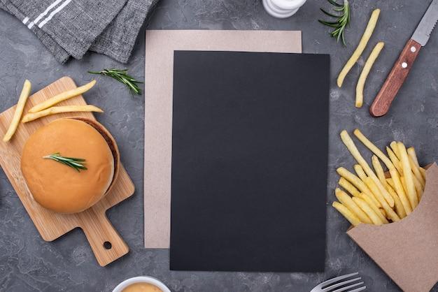 Blanco vel papier naast hamburger en frietjes Gratis Foto