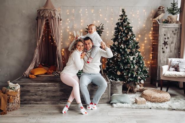 Blanke familie speelt thuis met hun jonge kind in een woonkamer met een kerstboom Gratis Foto