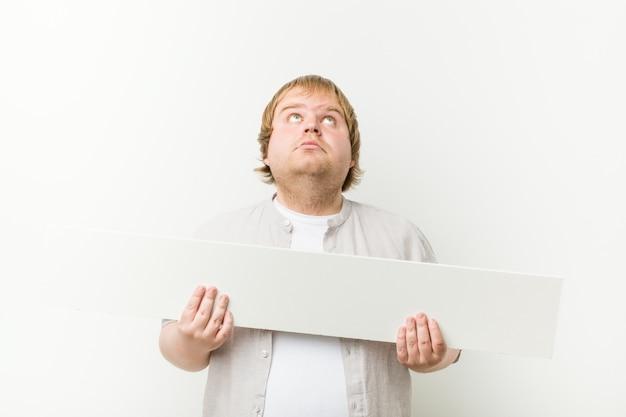 Blanke gekke blonde dikke man met een bordje Premium Foto
