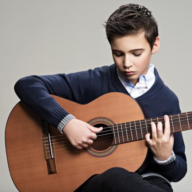 Blanke jongen spelen op akoestische gitaar. Gratis Foto