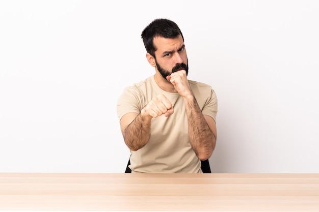 Blanke man met baard in een tafel met vechtgebaar. Premium Foto