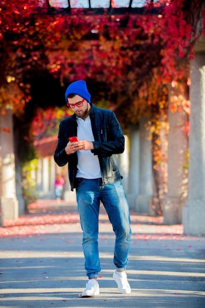 Blanke man met behulp van een mobiele telefoon in een park Premium Foto