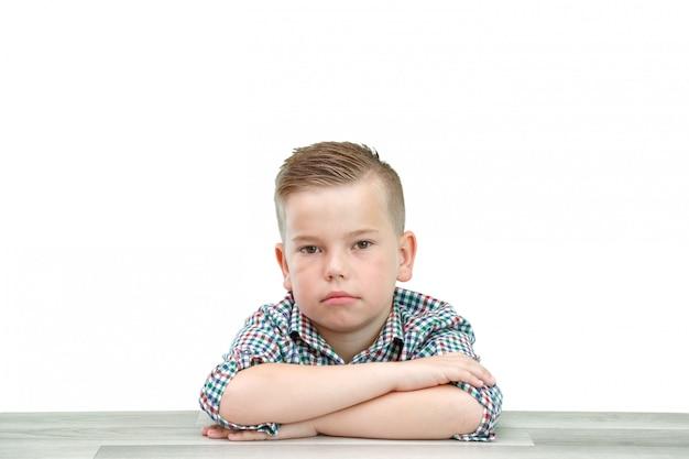 Blanke schoolgaande jongen in een plaid shirt op een licht geïsoleerde achtergrond zitten met zijn handen gevouwen Premium Foto