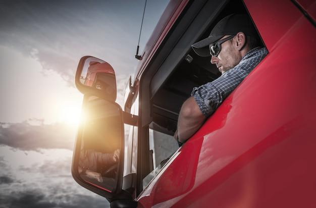 Blanke vrachtwagenchauffeur zich voorbereiden op de volgende bestemming. Premium Foto