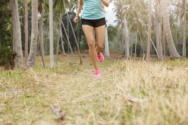 Blanke vrouw jogger met mooi fit lichaam draait op gras in tropisch woud. jonge vrouwelijke atleet die blauwe sporttop en zwarte broek draagt die buiten op zonnige dag uitoefent. Gratis Foto