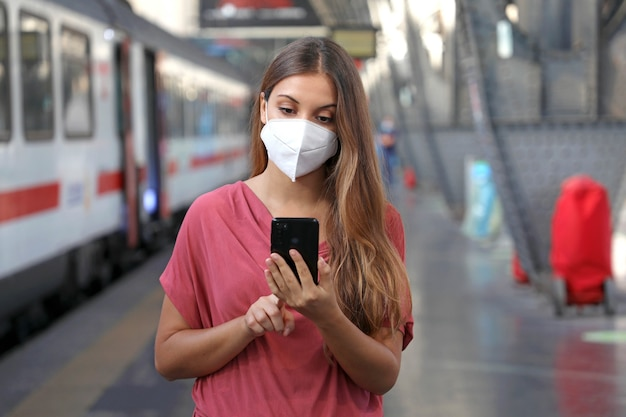 Blanke vrouw met behulp van slimme telefoon in het treinstation Premium Foto