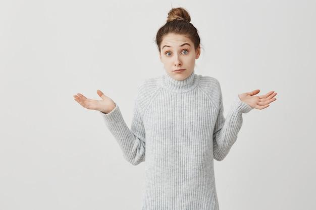 Blanke vrouw overgeven handen met onzekerheid op het gezicht. vrouwelijke startende ondernemer die zich gedraagt als heb geen idee of geeft niet om witte muur. emoties concept Gratis Foto