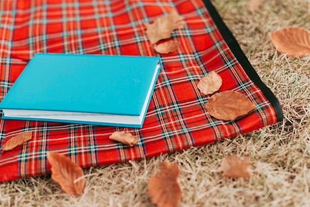 Blauw boek op picknickkleed met kopie ruimte Gratis Foto